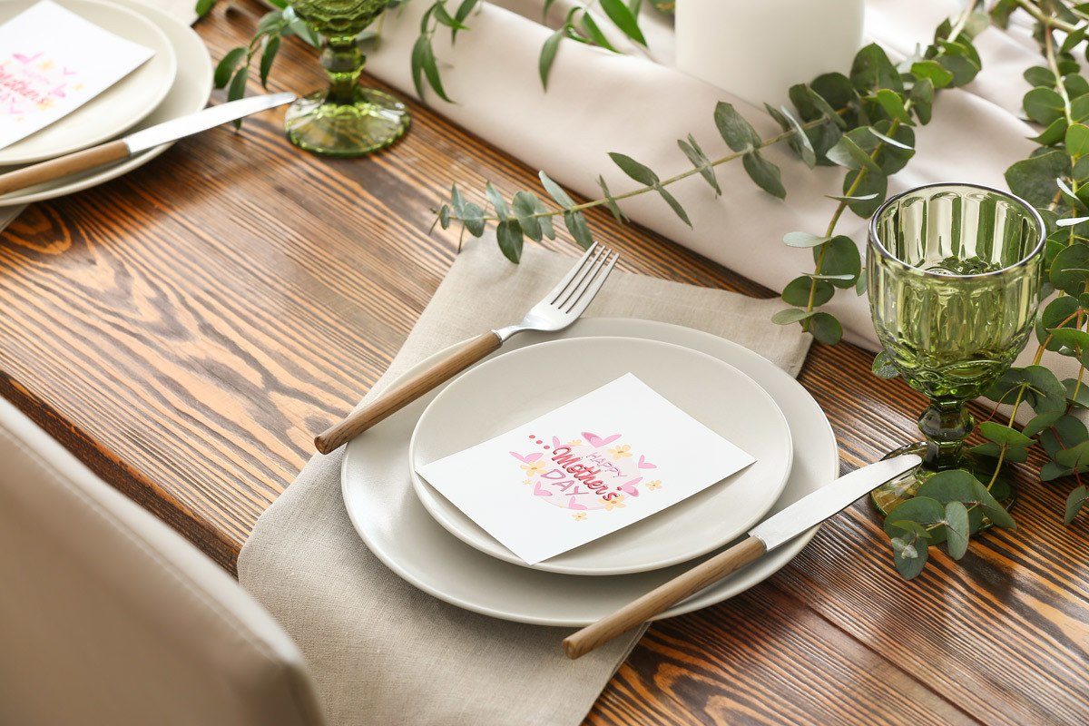 place setting at wood table with mothers day card place on top of plate