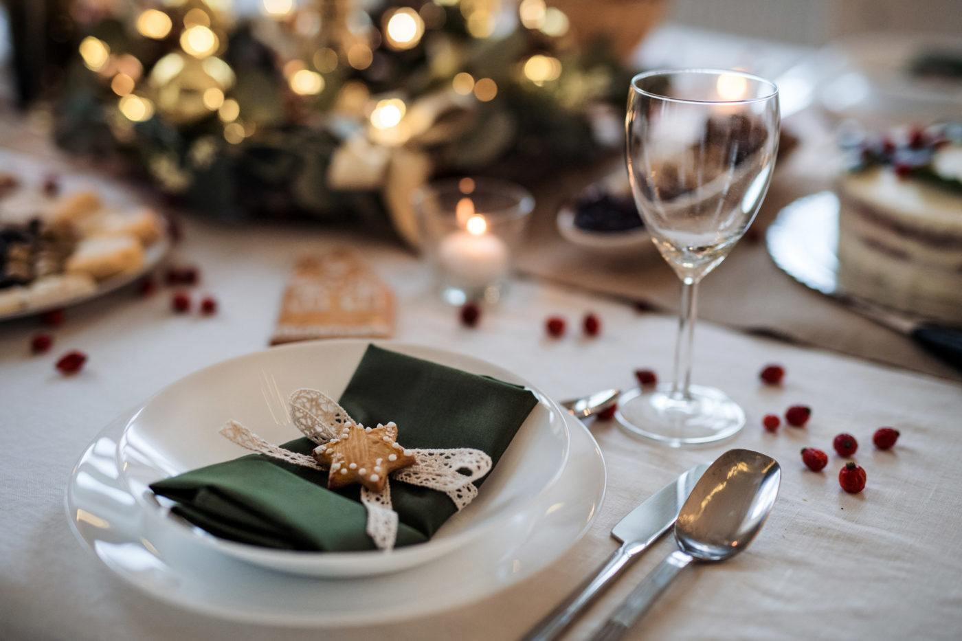 holiday table place setting with white plate and green napkin folded on top