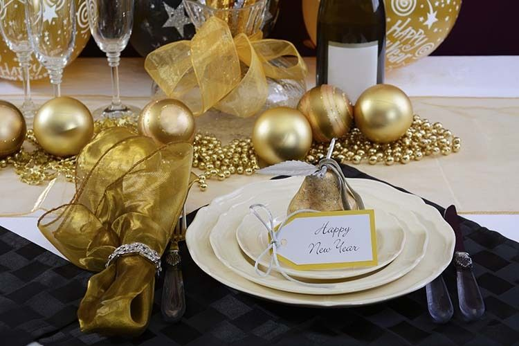 Happy New Years Eve elegant dinner table setting with black and gold decorations, balloons and stylish centerpiece, close up.