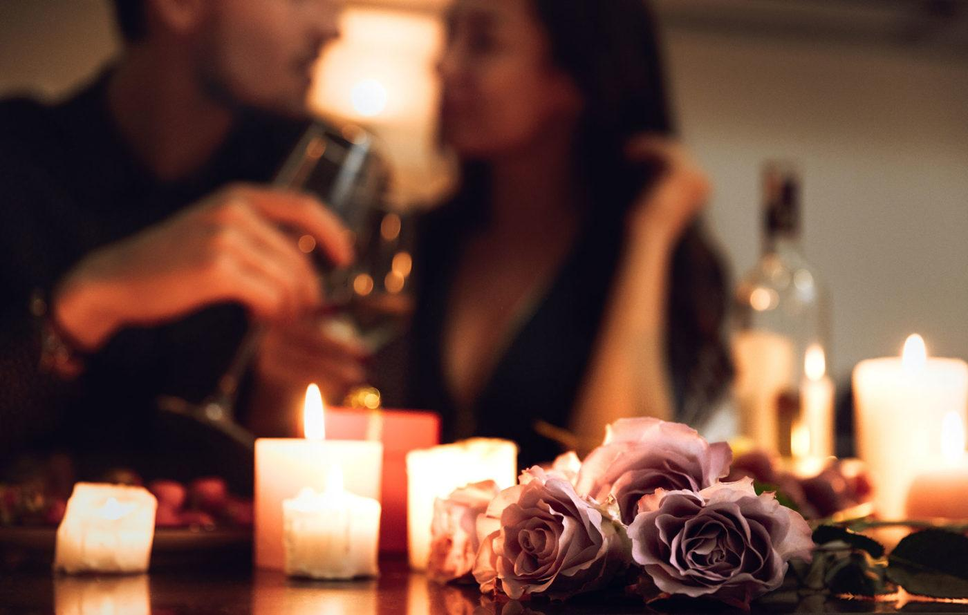roses and candles sitting on table with blurred couple in background